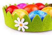 Barevné velikonoční vejce v zelené dekorace s heřmánkem — Stock fotografie