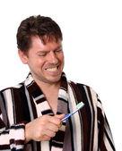 Man in bathrobe with toothbrush smiles — Stock Photo