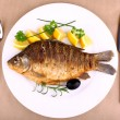 Fried fish on white plate with fork and knife — Stock Photo #21578535
