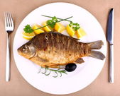 Fried fish on white plate with fork and knife — Stock Photo