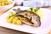 Whole grilled fish served with potatoes and lemon — Stock Photo