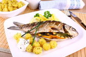 Whole grilled fish served with potatoes, lemon and sauce — Stock Photo