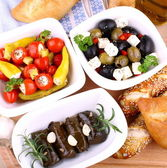 Vine leaves stuffed with peppers and Mediterranean antipasti — Stock Photo