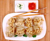 Dumplings on white plate with chopsticks and chilli sauce, view from top — Stock Photo