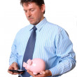 Businessman with piggy bank in hand calculate on the calculator — Stock Photo
