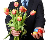 Man in suit and tie gives Easter eggs and tulips — Stock Photo