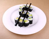 Sushi maki as dollar sign on white plate — Stock Photo