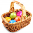 Wicker basket full of colorful Easter eggs — Stock Photo