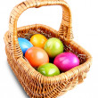 Wicker basket with colorful Easter eggs — Stock Photo