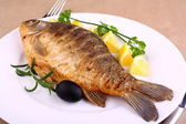 Fried fish on white plate with lemon, fork and knife — Stock Photo