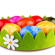 Colorful Easter eggs in green decoration and camomile — Stock Photo