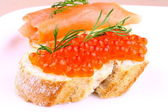 Large eggs red caviar on bread with dill — Stock Photo