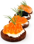 Pumpernickel bread with salmon, trout and sturgeon caviar — Stock Photo