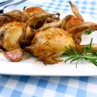 Four fried quail with gravy, garlic, rosemary, closeup - Stock Photo