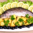 Baked trout with potatoes, black olives, lemon and salad — Stock Photo