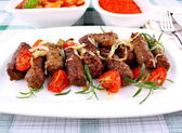 Grilled cevapcici with ajvar and giant white beans — Stock Photo