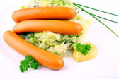 Three mini wieners on fried cabbage with mustard — Stock Photo