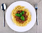 Delicious spaghetti bolognese with basil on white plate — Stock Photo