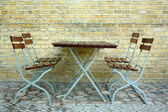 Four chairs and table in beer garden on brick wall — Stock Photo