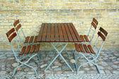 Vier stoelen en tafel in biertuin op bakstenen muur, bovenaanzicht — Stockfoto