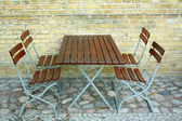 四个椅子和啤酒花园砖壁,顶视图中的表 — 图库照片