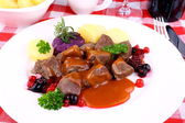 Deer goulash with potato, Burgundy sauce and wild berries — Stock Photo