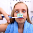 Blonde girl is surprised when brushing your teeth — Stock Photo