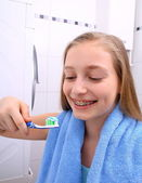 Blond girl with braces smiling while brushing your teeth — Stock Photo