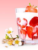 Ripe strawberries with white yogurt in glass, cereal, flowers — Stock Photo