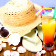 Red-yellow cocktail with summer hat, sunglasses — Stock Photo