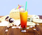 Red-yellow cocktail and summer hat, sunglasses — Stock Photo