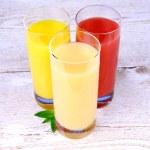 Oranges, bananas and grapefruit juice in glass — Stock Photo