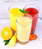 Tranche de bananes, de fraises et d'oranges, jus en verre — Photo