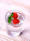 Water in glass with mint and two raspberries — Stock Photo