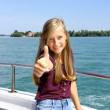 Happy young blonde girl shows ok sign on ship at sea — Stock Photo