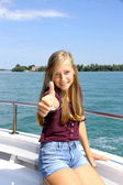 Happy young blonde girl shows ok sign on ship at sea — Foto Stock
