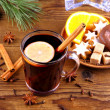 Mulled wine in glass with cinnamon stick and sweets — Stock Photo #34761123