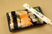 Assorted sushi with chopsticks in delivery box — Stock Photo