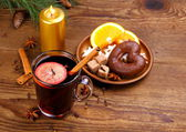 Mulled wine in glass with cinnamon stick and sweets — Stock Photo