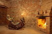 Vintage interior con mecedora por chimenea y velas — Foto de Stock