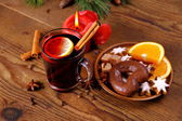 Mulled wine in glass with cinnamon stick, candle and sweets — Stock Photo