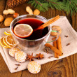 Mulled wine in glass with cinnamon stick, gingerbread and nuts — Stock Photo