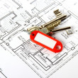Bunch of keys with red keychains at building drawing — Stock Photo
