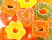 Colorful jelly candies in heart shape and gear as background — Stock Photo