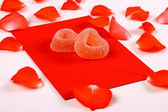 Two hearts from sugar candies on red envelope and petals — Stock Photo