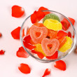 Colored candies with two red hearts in glass bowl and rose petals — Stock Photo #38350513