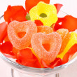 Colored candies with two red hearts in glass bowl and rose petals — Stock Photo