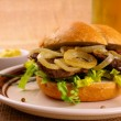 Grilled beef with onion rings in bun and beer — Stock Photo