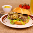 Grilled beef with onion rings in bun, mustard, beer — Stock Photo
