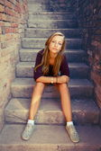 Sad girl with blue eyes sitting at stone brick stairs — Stock Photo